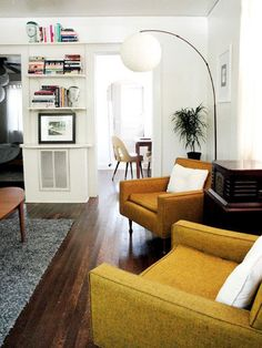 white walls, yellow chairs, dark wooden floors, oval coffee table, old fashion radio <3 totally us