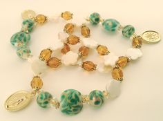 Our newest rosary bracelet: hand-made with hand-painted beads, Czech glass beads, and Mother of Pearl. It's already getting compliments as a staff favorite. Designed and made by Catholic women in the USA.