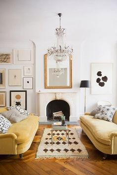 Domino magazine living room; mirror above fireplace, chandelier, abstract art wall gallery