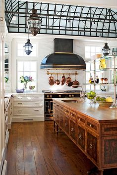 Oversized wooden center island looks like antique inlaid furniture, metal framed conservatory ceiling, black luxury oven range and hood, wide white lower cabinets
