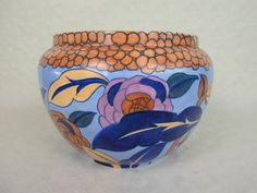 A 1920's Wood & Sons Bursley Ware jardiniere, designed by Charlotte Rhead, pattern no. 1432, having tube-lined stylized flowers and leaves on a blue ground, printed and tube-lined marks to base (17.5cm tall)