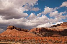 Dramatic puffy clouds over a desert landscape near Virgin Utah. Hurricane Mesa sticks out like a ship's prow.