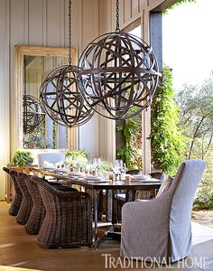 The banquet table in the outdoor dining room is graced by an enormous pair of bronzed chandeliers. - Photo: John Merkl / Design: Hillary Thomas