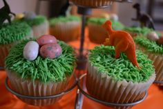 "Close up of the dino cupcakes I made this year for my daughter. Super easy to make! Boxed cake mix, green icing, ""grass"" frosting tip, ""dino eggs"" and party store dinosaurs :)"