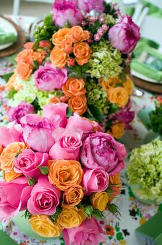 Pink and orange roses and peonies are perfect for a bright, festive centerpiece.