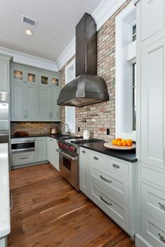 Shaker style kitchen in a gorgeous, timeless color. The hood is spectacular. So are the countertops -- concrete or?