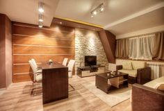 Expansive home office with wood and stone walls, wood floor, wood furniture. Includes large sitting area in addition to desk station
