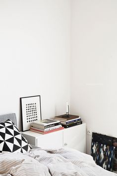 Modern minimalist white Scandinavian decorated interior design bedroom with big stacks of coffee table books, art and textiles