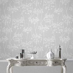 Flawlessly simple, this delicate sprig motif design stretches over a textured neutral base for the ultimate in easy living wallpaper. For a touch of luxury the grey and natural colourways have subtle glitter highlights.