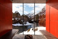 Modern minimalist red and concrete glass box with view of snow in Norway