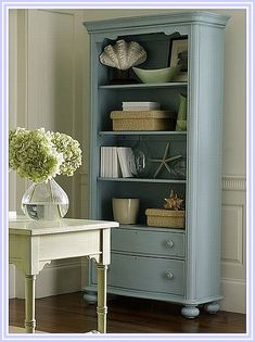 Beach Cottage Decor - Lovely vintage blue on the bookcase, filled with coastal nautical things but not too overdone...topped off with a classic vase  hydrangeas