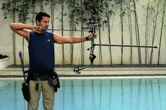 Standing 10 meters from the target, Richard Gomez pulls a pencil-thin arrow from the pouch on his hip. With his bow stave positioned toward the target, he aims and releases the arrow. It lands, piercing the board, which is as tough as cement. Asian Men, Cement, Arrow, Piercing, Target, Pouch, Pencil, Positivity