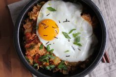 Enjoy this Kimchi Fried Rice Bowl fast! Hot and spicy and filled with bacon bits, kimchi and topped with a fried egg. You've got to try this.