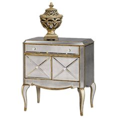 I like the mixed metallics. Reminiscent of Old Hollywood style, this mirrored wood chest features cabriole legs and an antiqued silver finish. Product: Chest