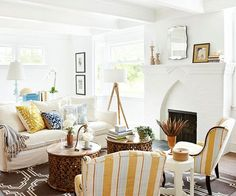 The living room's large windows, ceiling beams, and Gothic-style brick fireplace were among the original features that stood out most to the homeowners. They painted the walls, ceiling, and fireplace surround white to simplify the space and to reflect light streaming in from the windows. Featuring a palette of golden yellow, chocolate brown, and pale blue, the accessories ensure the all-white living space doesn't feel sterile and cold.