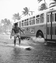 Rainstorm street surfer, Waikiki, Honolulu; captured by Warren Roll (1960)