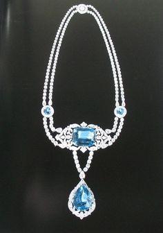 Ожерелье из парюры, состоящее из двух бриллиантовых ниток. В центре – ажурный элемент, усажанный бриллиантами, вставлен большой аквамарин огранки кушон., подвеской служит аквамарин грушевидной формы, окаймленный бриллиантами.