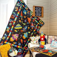 Make a colourful and dramatic quilt for the budding astronaut in your family using Gillian Grimmett's quilt pattern. Combine appliquéd rockets, spaceship, planets and stars with a scrappy patchwork border for a quilt that's out of this world.