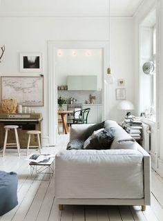 light wooden floors, light couch, white walls, framed map