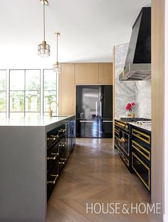 Designers Michelle Lloyd Bermann and Christine Ralphs ensured the black cabinets were given brass accents to coordinate with the black La Cornue stove in hockey star Jason Arnott's home.   Photographer: Nathan Schroder   Designer: Lloyd Ralphs Design