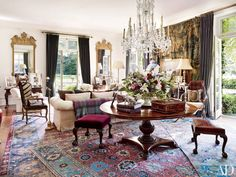 The living room of fashion designer Ralph Lauren's Bedford, New York, estate, features an arrangement of 17th- and 18th-century Persian carpets. A Victorian cut-glass chandelier, a pair of George II gilt-wood mirrors, and a 16th-century Flemish tapestry also embellish the space.