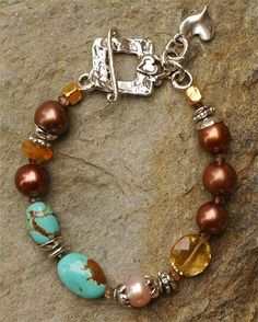 ~Treasures of the Earth... Natural treasures from the Earth! Rare Number 8 Turquoise with a gem quality coin shaped Citrine, tiny faceted Andaluscite and luscious chocolate Freshwater Pearls. The sterling silver toggle is our own design--with a heart adorned upon it. Bracelet is a size 8.5 Fits a wrist size 7.0 perfectly A custom size can be made just for you! An Original Artisan bracelet by Cathy Dailey