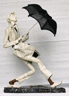 .paper mache? do not know the artist but clothes are newsprint-wonderful work