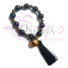 Pulsera elástica con perlas esmaltadas y borla de color negro.