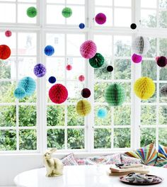 20 creative ways to decorate your home and beyond with honeycomb paper pom poms, including pom pom mobiles, gift wrap inspiration and wedding decs.