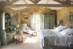 Distressed wood surfaces, regional yellow pottery, and accessories such as a wild boar tavern sign reflect the architecture's rustic style. The contrast of a fancy trumeau against a wall only heightens the rough and humble feel of the place. Antique painted furniture complements the master bedroom's rustic architecture.    - Veranda.com