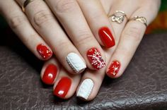 Beautiful winter nail art with a snowflake pattern. Rhinestones in the center of a snowflake. The color is red and white.