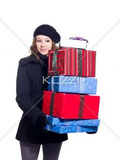 beautiful young woman holding a stack of christmas presents. - Beautiful young woman holding a stack of Christmas presents over white background, Model: Brittany Beaudoin