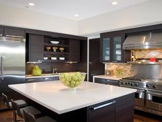 This contemporary kitchen design features an open design with a kitchen island, dark cabinets, stainless steel appliances and white countertops. A tiled backsplash adds some small color to the white and brown kitchen.