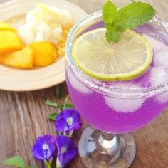 Color-changing pink iced tea with mango sticky rice. Steep a couple of butterfly pea flowers in hot water for 3 minutes strain and add ice cubes. Dip a wet glas into sugar then fill with the blue tea from butterfly pea flowers add lemon juice and stir. The tea is now pink for decoration add mint and lemon slices. The mango sticky rice is hard to come by if you're not living in tropic regions. #Repost @blue.chai