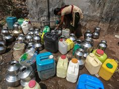 A woman fills water containers at a public faucet in Babhalichi Bhat village near Mumbai, India. More than 500 people depend on this single water source which runs for only one hour five days in a week.  Divyakant Solanki, European Pressphoto Agency