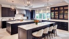 Transitional kitchen with black cabinets; white and gray marble countertops | Laura U. Interior Design