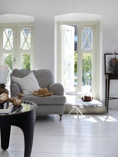 huge windows, great lighting, white floors, and that striped chair is beautiful, it looks like a nice place to read