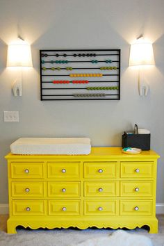 Vintage dresser (turned changing table) painted in a bold pop of yellow, with grey walls provides a perfect serene backdrop for the other more neutral elements.