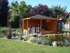 Mit einem offenen Gartenhaus sind Sie zwar draußen, gleichzeitig aber vor Wind und Wetter geschützt. Die 5-Eck Gartenlaube Maik ist charmant am Gartenteich platziert.