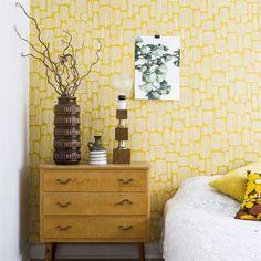 Sovrum i gult. Sovrumsväggarna är klädda med tapeten Miss Print från Midbec. På sängen ligger ett överkast som Idas mamma virkat. Byrå och vaser från loppis, liksom printet Märta my dear.