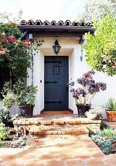 & Trends Charming Spanish-inspired home exterior with succulent landscaping, hanging iron lantern and painted black front door.Charming Spanish-inspired home exterior with succulent landscaping, hanging iron lantern and painted black front door. Spanish Bungalow, Spanish Style Homes, Spanish House, Spanish Colonial, Spanish Revival Home, Spanish Pool, Front Door Paint Colors, Painted Front Doors, Mission Style Homes