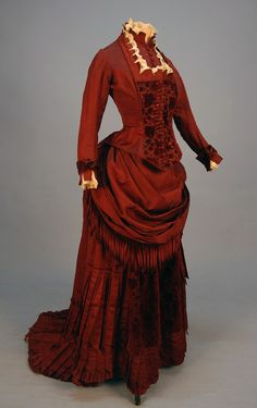 SILK and VELVET BUSTLE DRESS with FRINGE, c. 1880. Claret ottoman with self piping, lace and crenelated trim at neck, bib front and cuff, floral cut velvet bodice and skirt front panel, draped skirt trimmed in chenille fringe and pointed pleats, crocheted buttons, polished cotton lining. B-30, W-22, skirt front L-37, back L-52. (Faint underarm stains, two buttons need to be resewn, waistband replaced, train relined and altered to button on to skirt hem) very good.