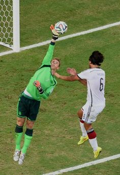 Germany's goalkeeper Manuel Neuer, left, leaps and palms the ball as his teammate Sami Khedira  jumps during the group G World Cup soccer match between Germany and Ghana at the Arena Castelao in Fortaleza, Brazil, Saturday, June 21, 2014