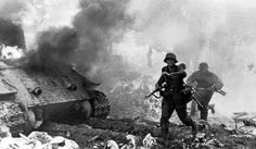 German Panzergrenadiers from the 3rd SS Panzer Division Totenkopf pass behind a destroyed Soviet T-34/85, 1944.