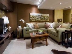 Small basement family room with brown and yellow walls, and a square, green sectional couch, with a small coffee table.