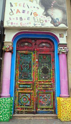 Doorway in Paris, France; Purple pillars; Multicolored, painted, carved door.
