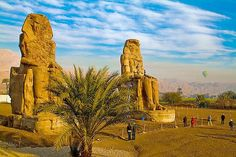 The Colossi of Memnon are two enormous stone statues of Pharaoh Amenhotep the 3rd. since 1350 before century they have stood in the Theban necropolis, across the River Nile from the modern city of Luxor.