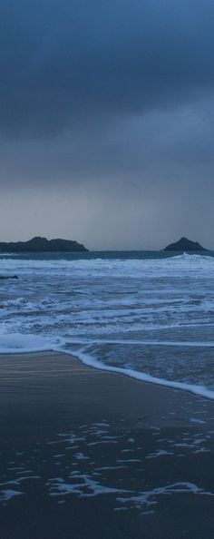 Stormy seas and approaching rain from a deserted beach at Lundy Bay in North Cornwall, England.