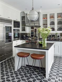 Traditional kitchen with black and white printed tiles, a retro pendant light over a small kitchen island with wooden barstools
