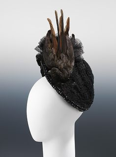 "Evening Bonnet: ca. 1880, French (probably), silk, birds, feathers, jet. ""This evening hat features a dramatic use and placement of whole birds. Rather than being integrated into the shape of the hat, the birds, combined with the vertical point d'esprit are used to create a dramatic sense of upward movement and height.""    NOTE: Whole birds. Ew."